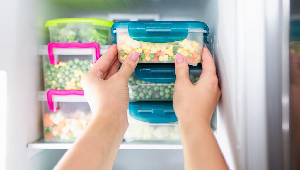 Kobieta wyciąga mrożone warzywa zzamrażarki