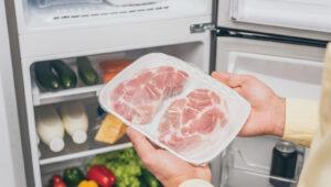 mężczyzna wyciąga zamrożone mięso zzamrażarki